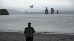 Man catches quadcopter in beach of Pacific Coast after flying and shooting Footage