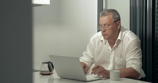 Serious adult man working on laptop while drinking coffee in kitchen Footage