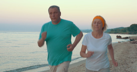 Mature Couple Jogging on the Beach Footage