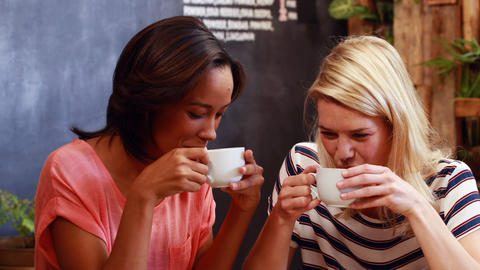Friends drinking coffee and looking at smartphone Live Action