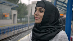 Young dreaming muslim woman in hijab is waiting for train, religion concept Footage