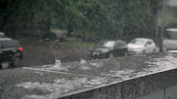 drops of rain fall on curb, cars on background, weather concept, urban concept Footage