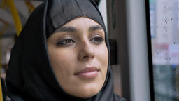 Face of young sweet muslim woman in hijab is watching in rainy window in bus Footage
