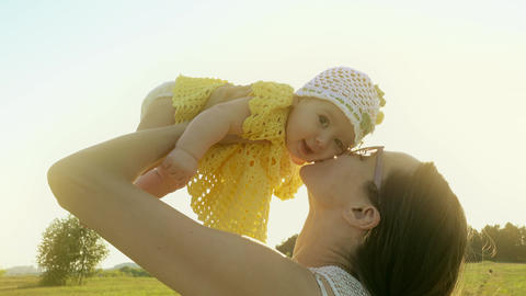 Happy mom holding her smiling baby girl against shining sun GIF