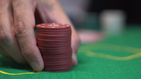 Gambler make bet, pushing stack of red poker chips towards on casino green table ビデオ