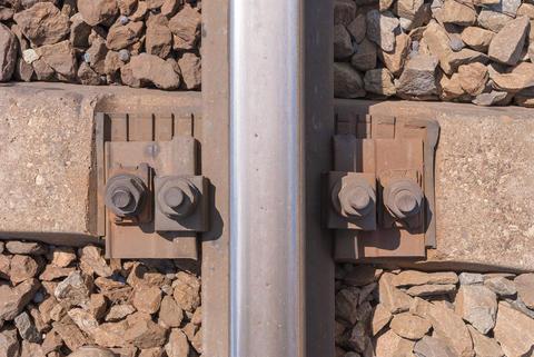 Steel rail fixed to a concrete sleeper Photo