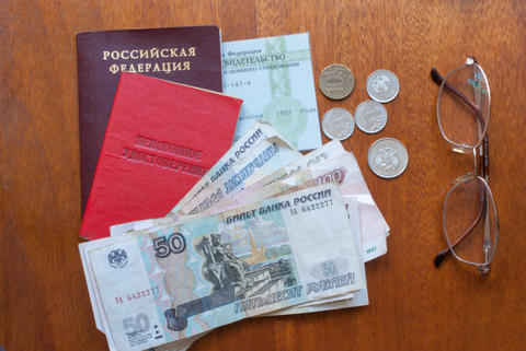 money, glasses and pension certificate on a wooden surface - russian translation Fotografía