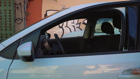 Woman put a jacket on the car seat and sits down on the driver's seat, intending Live Action