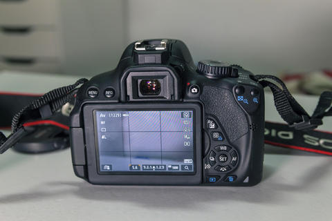Closeup of modern black DSLR camera on white table フォト