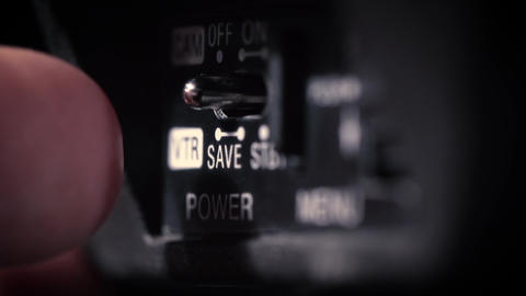 Hand pressing ON-OFF button on television camera Footage