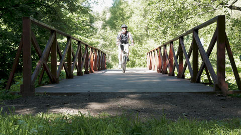 A man is riding a bicycle in the park. In summer time Footage