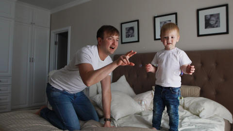 Dad plays with his son in the bedroom catching soap bubbles smiling and laughing Footage