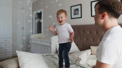 Caring father plays son looking at soap bubbles, the boy is happy jumping on the Footage