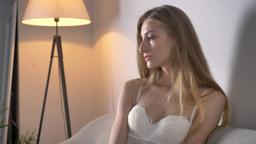 Portrait of young pretty blonde women in bra sitting on sofa and looking into Footage