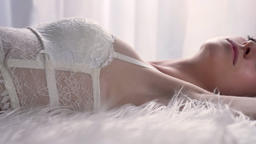 Portrait of young sexy attractive women in bra lying on bed with fur and looking Footage