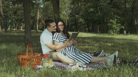 Happy pregnant family resting in summer park GIF