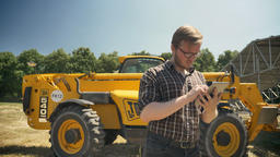 Young male farmer in glasses standing on straw field and using tablet Footage