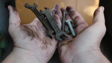 Man's dirty hands hold various tools and then drop them Footage