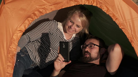 A happy couple in a tent is watching something on the phone and laughing Archivo