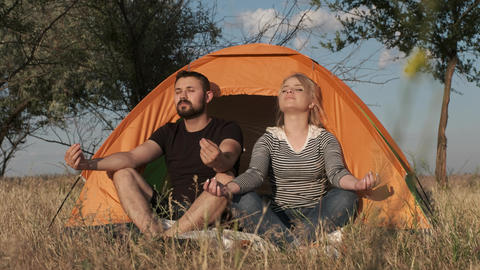 Two people in a tent meditate together Live Action