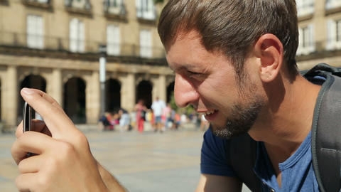 Traveler taking panorama picture of city square with his mobile phone, close-up Footage