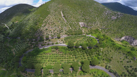 Aerial view of beautiful mountains, winding road between trees and bushes Footage
