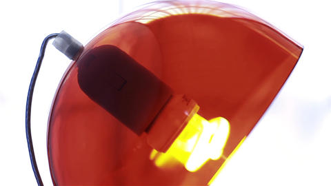 Light Bulb On Red Lamp Turning On. Zoom In. Close-Up Footage