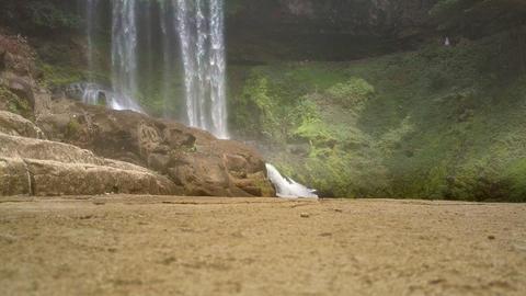 huge brown boulders against powerful waterfall Footage