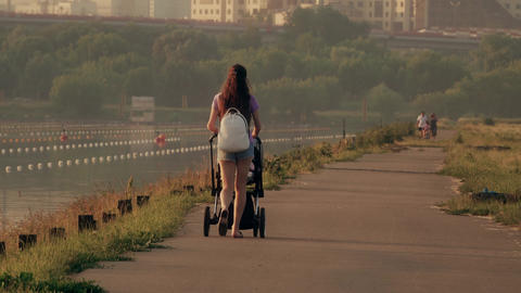 Beautiful young woman pushing stroller along waterfront pathway Footage