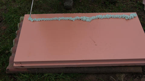 Spraying Fix Foam glue on pink polystyrene block for insulation Footage