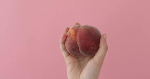 Juicy peach in female hands on pink background Footage