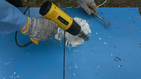 Scraping removing old blue paint from old wooden cupboard Footage