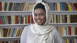 Young charming african muslim girl in hijab is watching at camera, smiling Footage