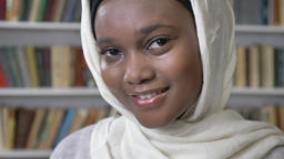 Face of young charming african muslim girl in hijab is watching at camera Footage