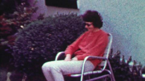 1965: Drug addict sunglasses woman enjoys rocking lawn chair Footage