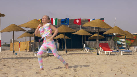 Happy girl dancing on summer beach on background international flags GIF