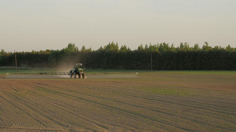 Tractor spray field with chemicals for crop plants protection from weed and pest Footage