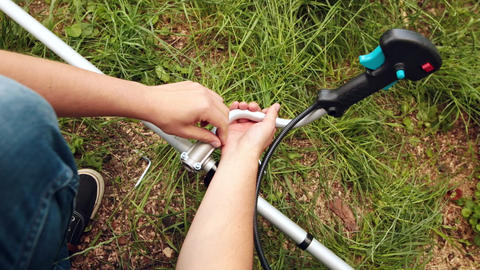 Young farmer fixes the handle on the bar of string trimmer Live Action