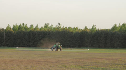 Tractor spray fertilize field with insecticide herbicide chemicals in Footage