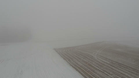 Misty winter morning farm field with stubble and snow, aerial Archivo