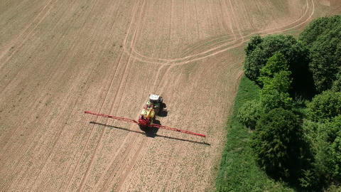 tractor in spring spraying farm field with crop sprouts, aerial ビデオ