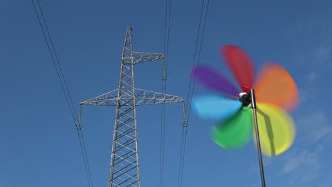 Windmill toy alternative energy symbol and electricity tower Footage