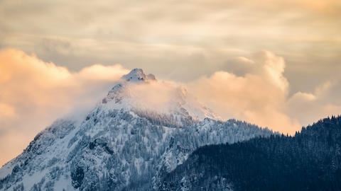 Evening clouds over alpine peak in winter Time lapse Live Action