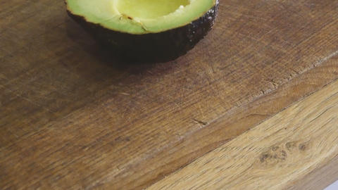 tracking shot on wooden cutting board and avocado cut in two ビデオ