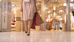 Legs of young girl goes shopping in mall, holds bags, shopping concept, fashion Footage
