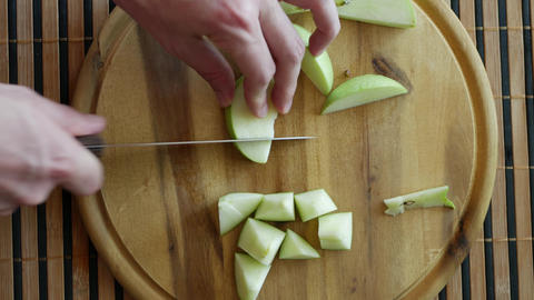 Slicing green apple pieces on board top-view Footage