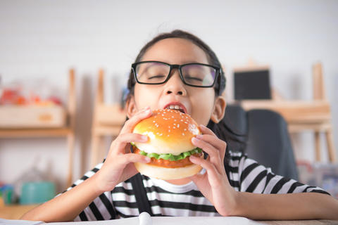 Asian little girl eating hamburger on wooden table select focus Photo
