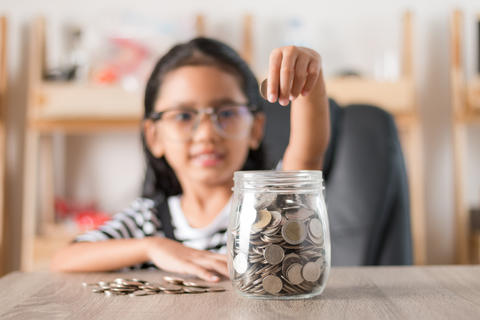 Asian little girl in putting coin in to glass jar shallow depth フォト