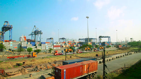 Container truck moves into shipping yard holding stacks of shipping containers Live Action