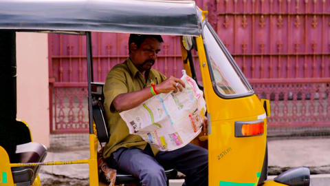 A auto rickshaw driver reading a newspaper in India Live Action